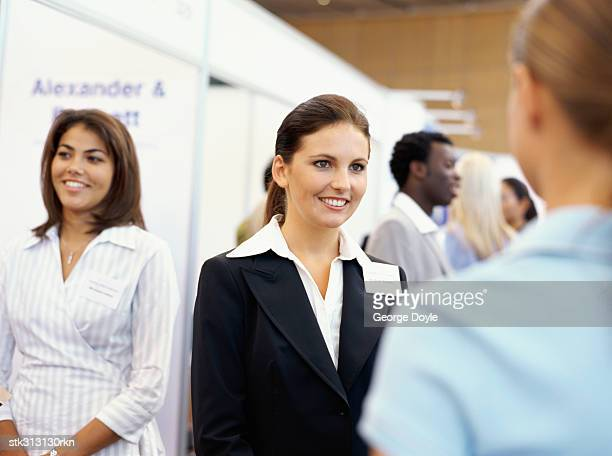 three businesswomen at an exhibition - tradeshow stock pictures, royalty-free photos & images
