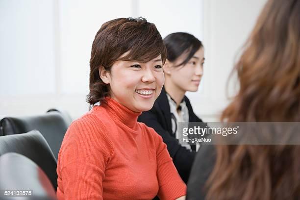 3 businesswomen で、コンファレンステーブルを中心に、笑顔の女性のクローズアップ