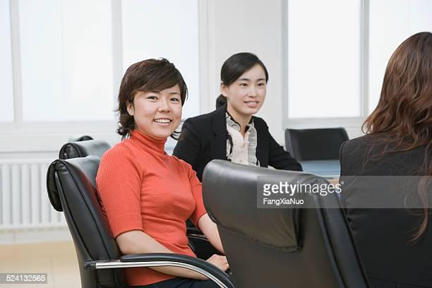 3 つの businesswomen コンファレンステーブル、笑顔で