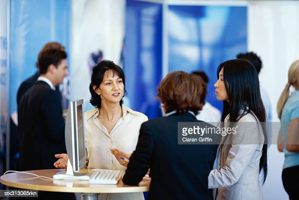 three businesswomen discussing at an exhibition - tradeshow stock pictures, royalty-free photos & images