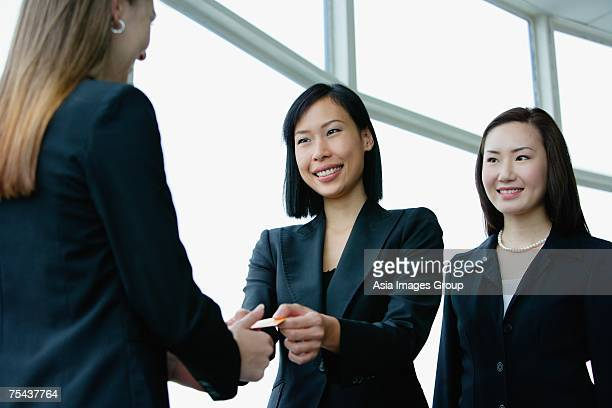 Three businesswomen exchanging business cards