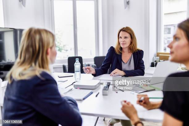 three businesswomen having a meeting in office - human resources stock pictures, royalty-free photos & images