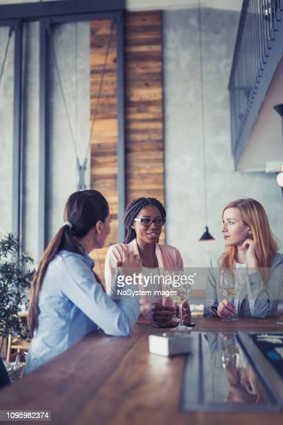 three businesswomen having drink at bar after work - happy hour stock pictures, royalty-free photos & images