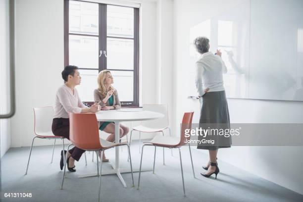 three businesswomen in meeting room, one using whiteboard - mondo naturale foto e immagini stock