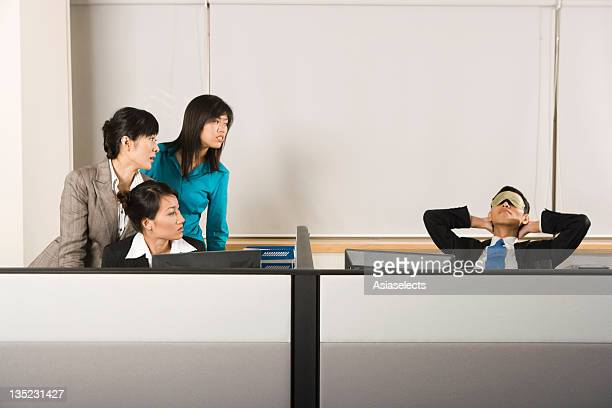 Three businesswomen looking at a businessman sleeping on a chair in an office