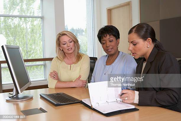 Three businesswomen looking at personal organizer during meeting