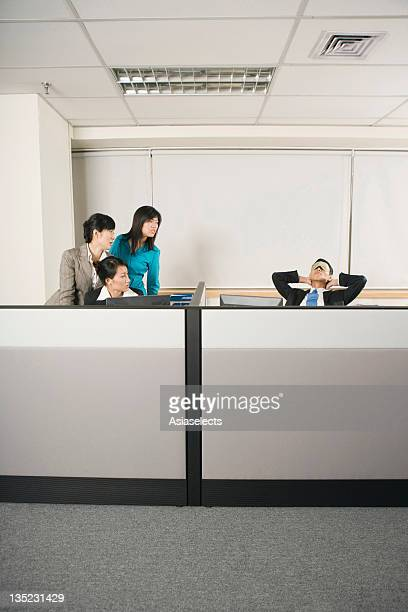 Three businesswomen looking at their colleague napping on a chair