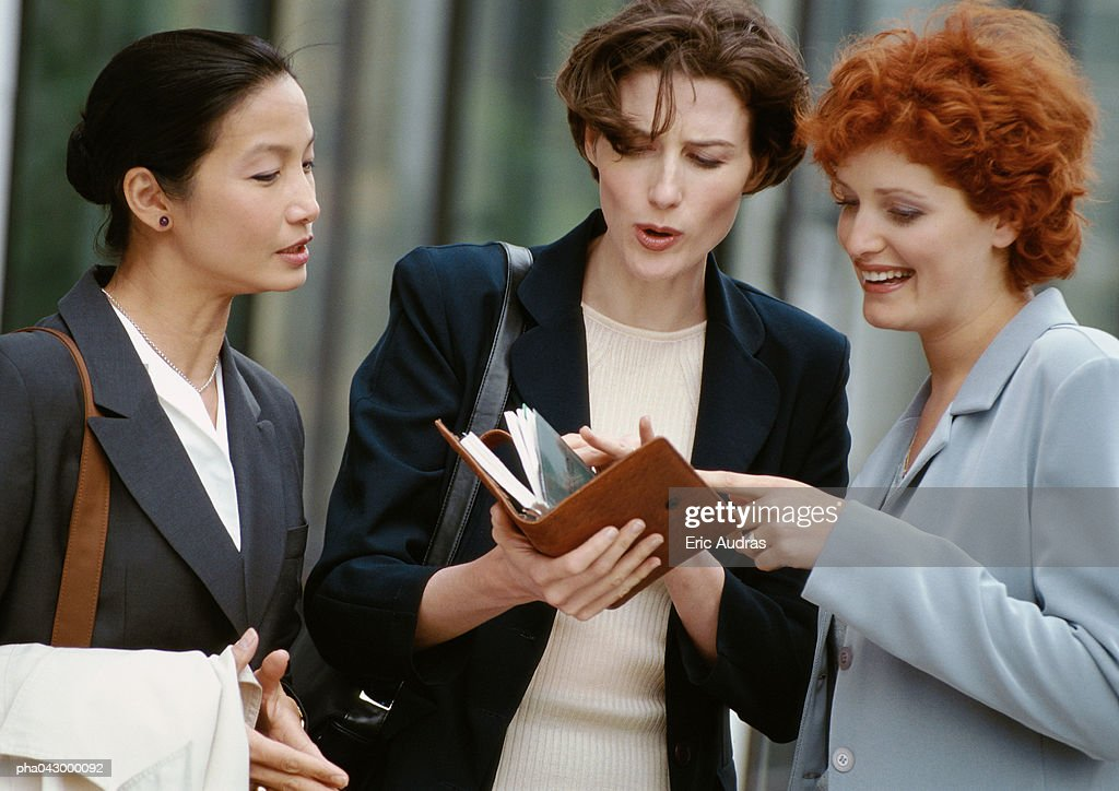 Three businesswomen side by side, one holding diary : Stockfoto