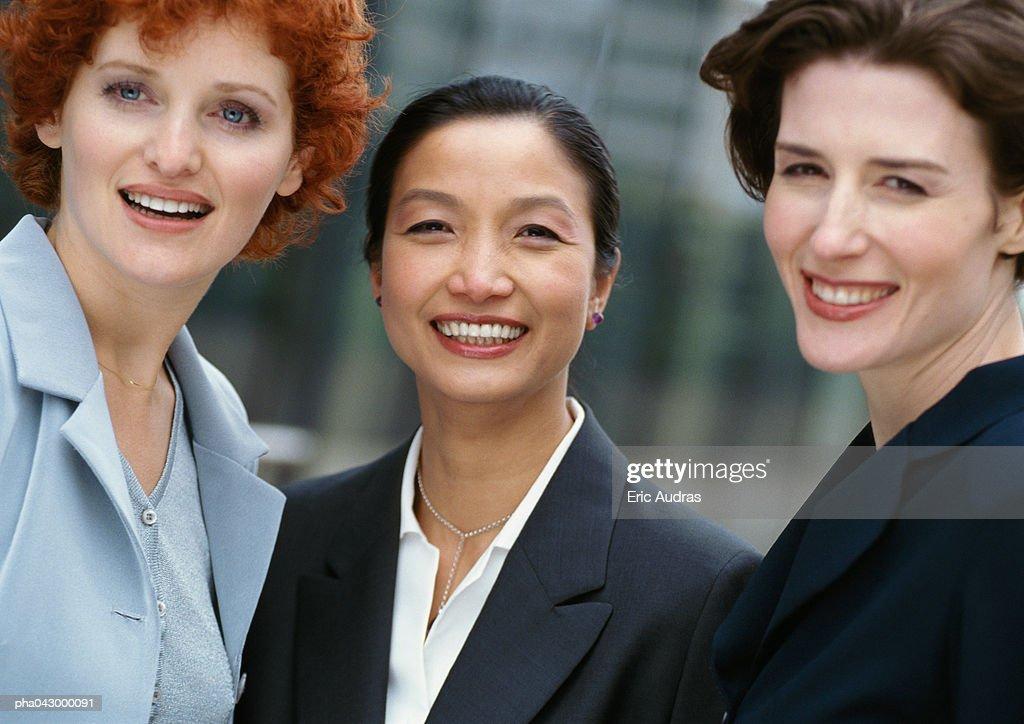 Three businesswomen side by side, smiling : Stockfoto