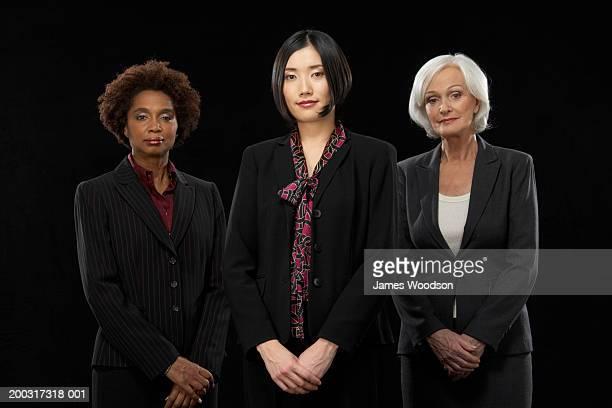 Three businesswomen standing together smiling, portrait