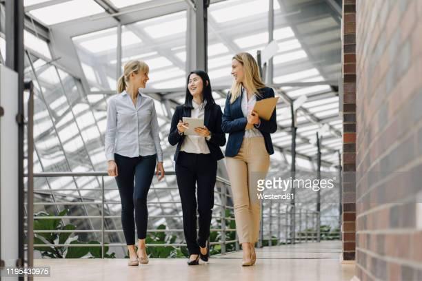 three businesswomen with tablet walking and talking in modern office building - weibliche führungskraft stock-fotos und bilder