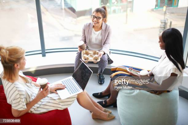 Three businesswomen with takeaway coffee sitting on beanbags chatting