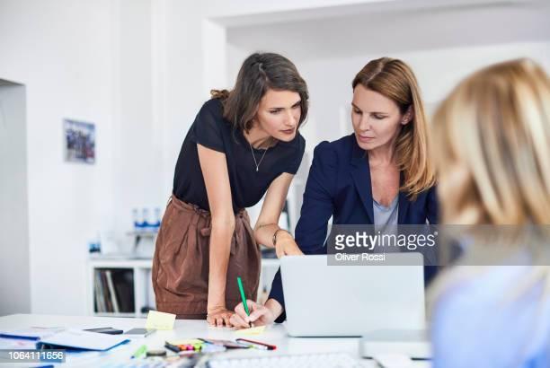 three businesswomen working at desk in office - frauenpower stock-fotos und bilder
