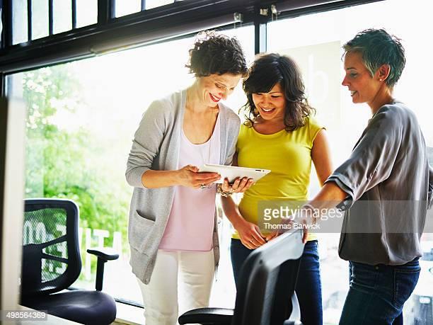 Three businesswomen working on digital tablet