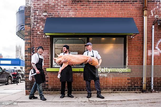 Trois bouchers à l'extérieur de leur boucherie tenant un cochon