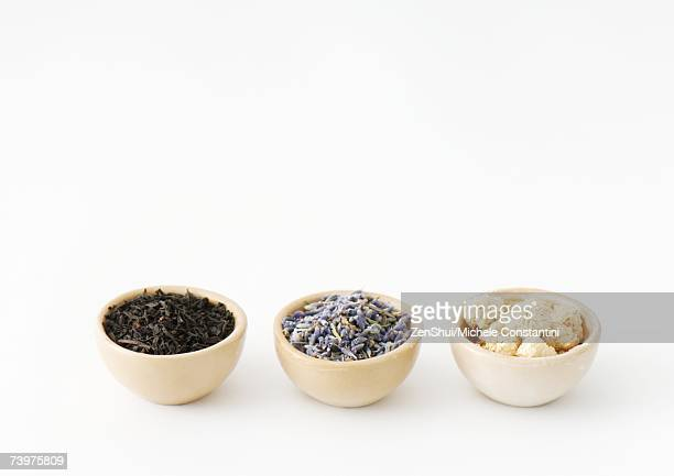 Three calabash bowls containing tea leaves, lavender, and chamomile flowers