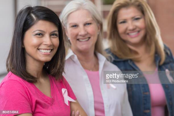 Three cancer survivors stand side by side and smile