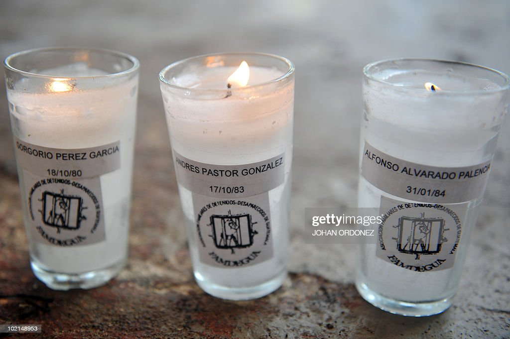 Three candles bearing the names of three Guatemalan disappeared during the armed conflict (1960-1996) are on display during a ceremony on June 16, 2010 at the La Verbene cemetery, in Guatemala City, where a search is taking place to recover the bodies of at least 889 people from four common graves. AFP PHOTO / Johan ORDONEZ