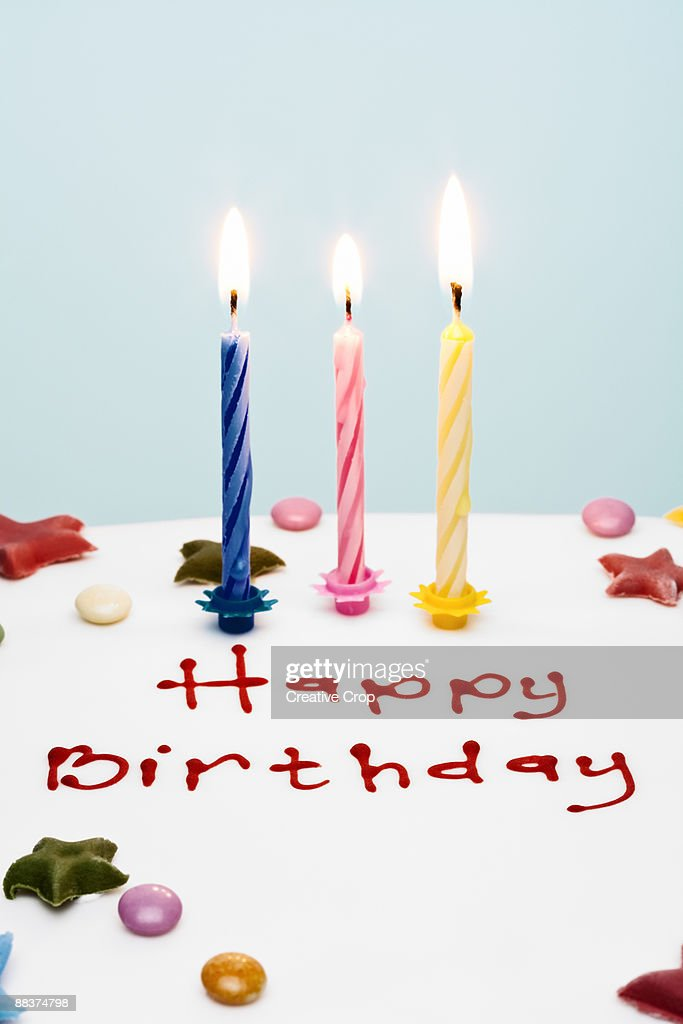 Three Candles On Birthday Cake With Happy Birthday Stock Photo