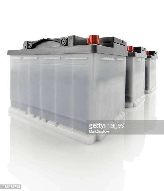 Three car batteries against a white background
