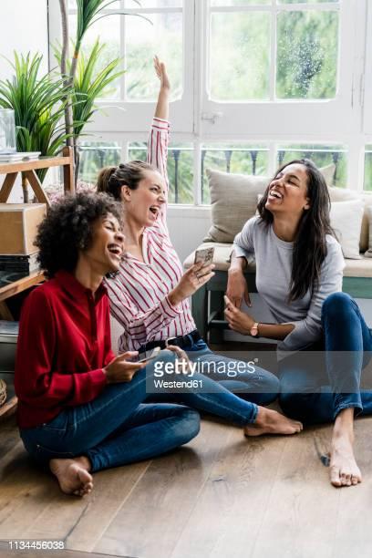 three carefree women sitting on the floor at home with cell phones - weibliche freundschaft stock-fotos und bilder