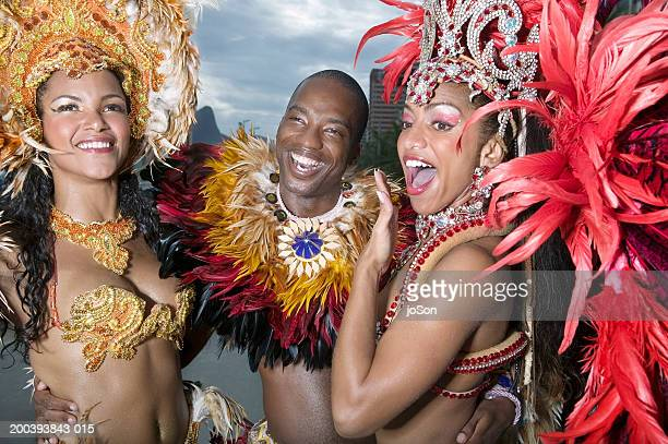 Three carnival dancers wearing festive costumes, smiling, close-up