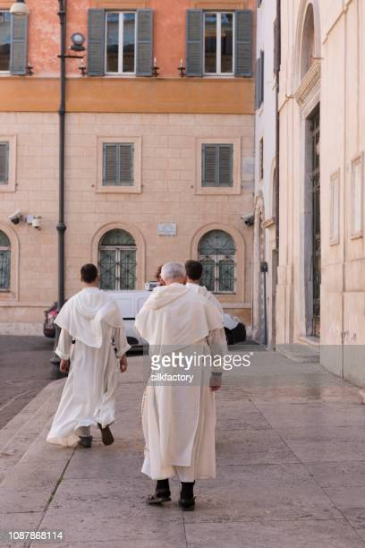 three catholic brothers walking together in rome - cleric stock pictures, royalty-free photos & images