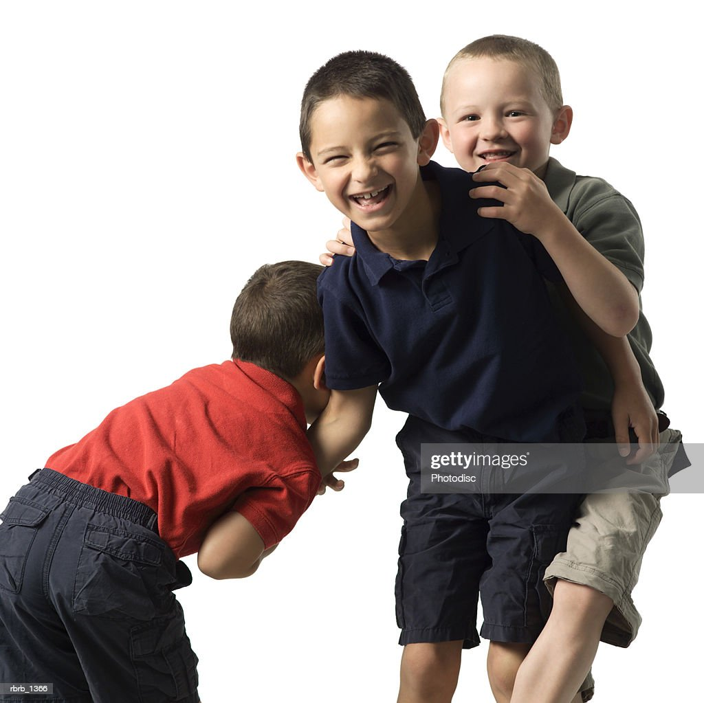 three caucasian child brothers play and fight with each other : Stockfoto