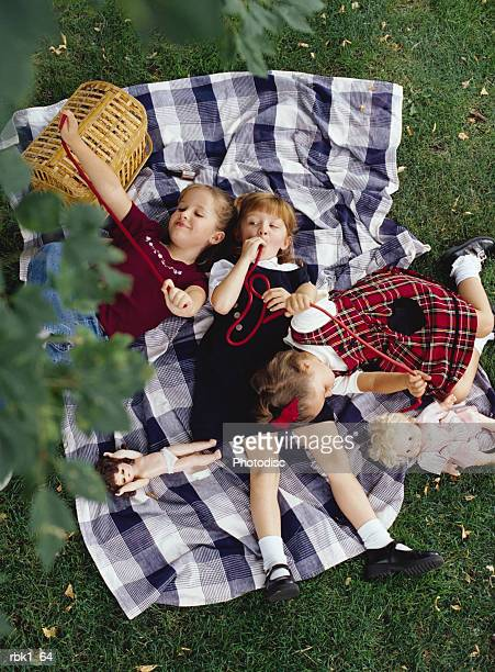 Three caucasian girls lie on a picnic blanket and eat licorice in a park