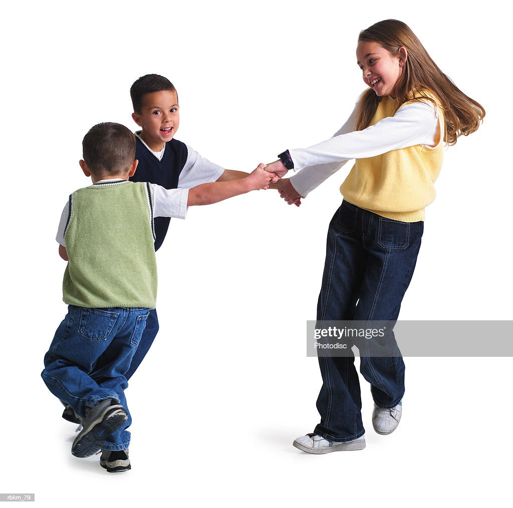 three caucasian siblings hold hand and spin around while playing together : Stockfoto