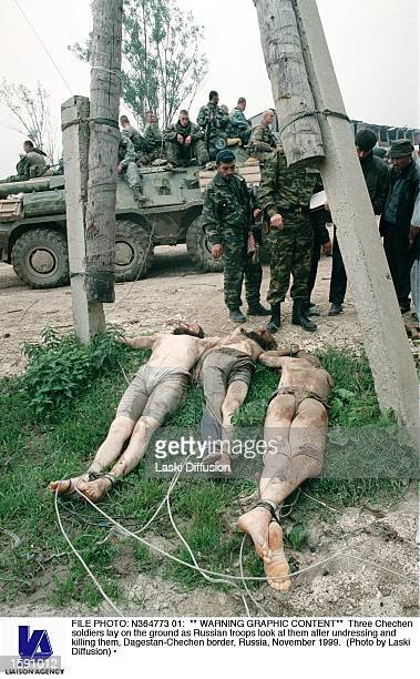 CONTENT** Three Chechen soldiers lay on the ground as Russian troops look at them after undressing and killing them DagestanChechen border Russia...