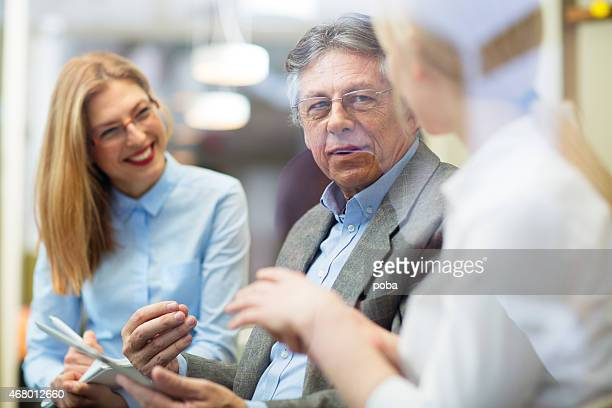 Three cheerful businesspeople discussing in a meeting