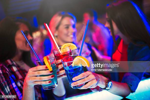Three cheerful female friends having fun in night club