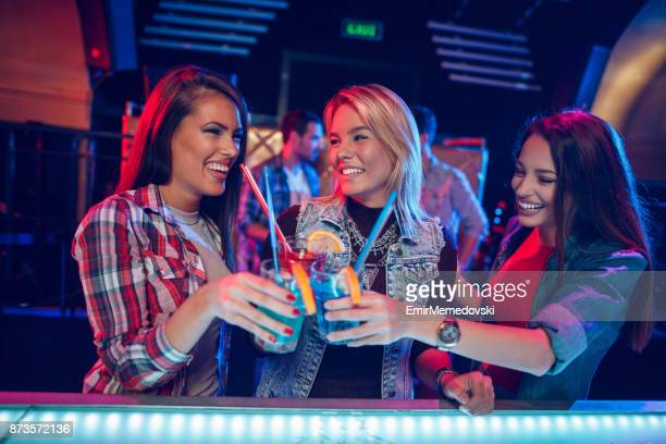 Three cheerful female friends having fun in nightclub