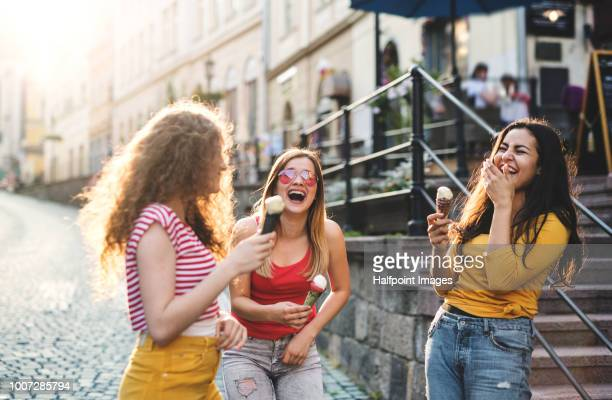 Three cheerful female teenager friends with ice cream standing on the street, laughing.