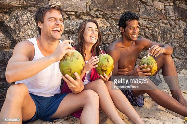 Three cheerful friends enjoying coconut drinks on beach.