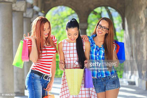 Three cheerful girls looking at their new purchases