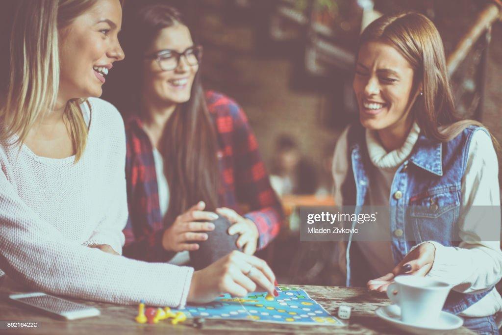 Three cheerful  girls playing board game. : Stock Photo