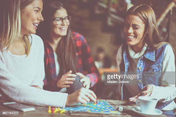 Three cheerful  girls playing board game.