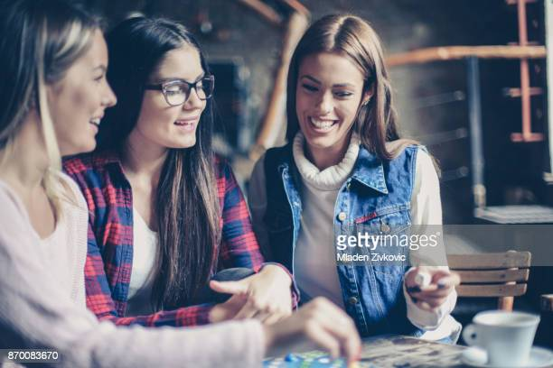 three cheerful  girls playing board game. - board game stock pictures, royalty-free photos & images