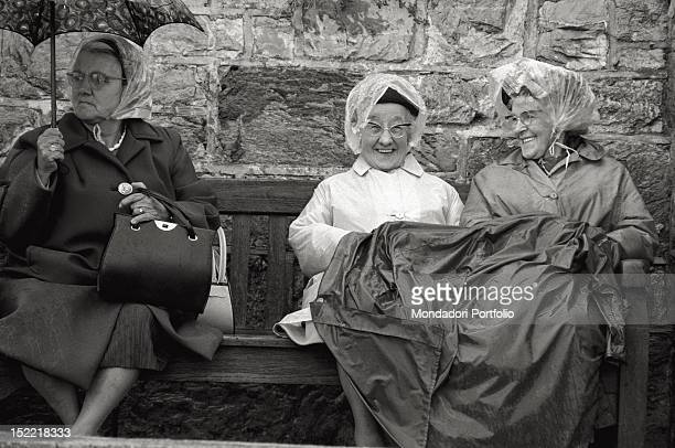 Three cheerful old ladies seated on a bench under the rain, protecting themselves with umbrellas, raincoats and waxed jackets, wait for the arrival...