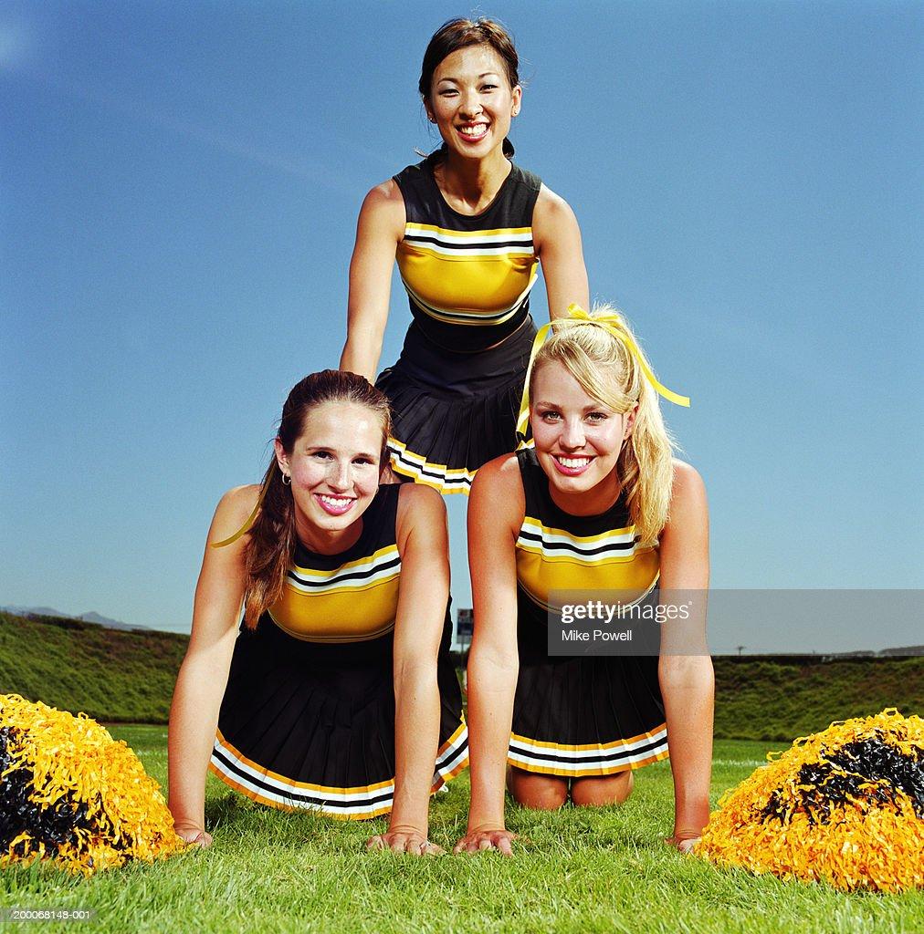 Three cheerleaders forming human pyramid on field, portrait : Stock Photo