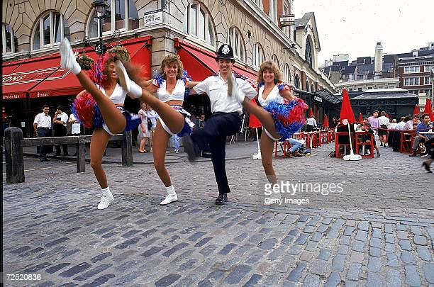 Three cheerleaders perform their routine with an English policeman in Covent Garden Market London prior to the American Bowl Mandatory Credit...