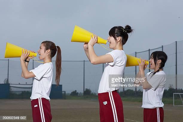 Three cheerleaders (15-18) shouting into megaphones, side view