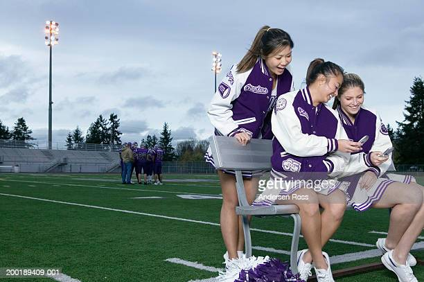 three cheerleaders (16-18) using cell phones beside football field - asian cheerleaders stock photos and pictures