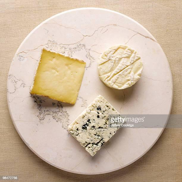 three cheeses on stone - kaasplank stockfoto's en -beelden