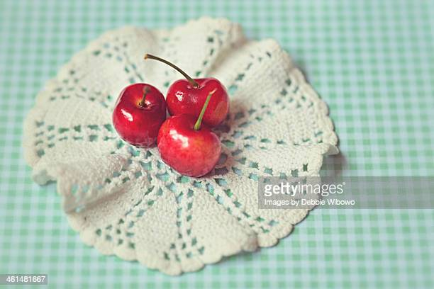 Three cherries on a white lace doilies