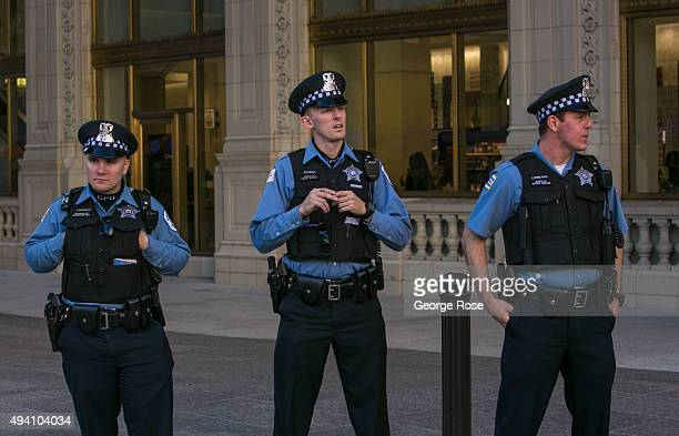 Three Chicago police officers stand guard at the entrance to the Wrigley Building on October 10 2015 in Chicago Illinois Chicago the third largest...