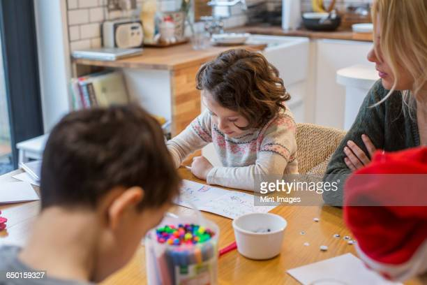 Three children and an adult woman at a table, drawing and writing cards and letters to Santa.