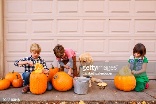 Three children and their dog carving Halloween pumpkins
